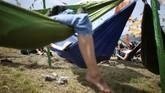 Tempat tidur gantung jadi alternatif menyenangkan untuk sekadar menikmati sinar matahari, sampai tidur. (REUTERS/Henry Nicholls)