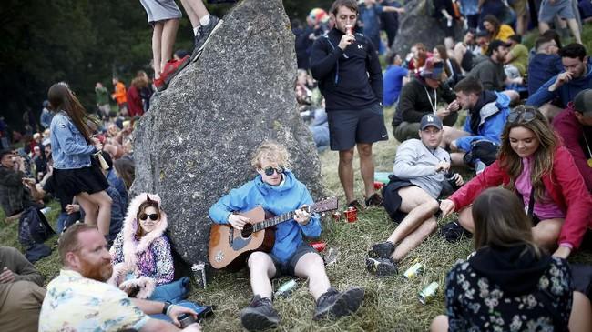 Tak sedikit yang memilih bersantai saja sembari berkumpul dan memainkan musik di atas rumput, di antara batu-batu besar di peternakan Worthy di Somerset. (REUTERS/Henry Nicholls)
