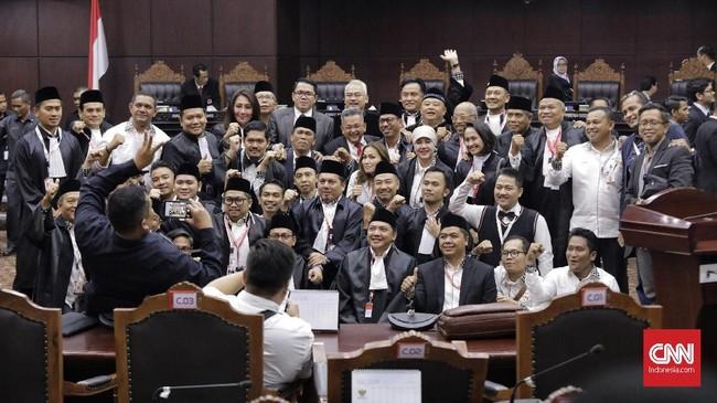 Tim kuasa hukum dan tim pendamping Jokowi-Ma'ruf berfoto bersama di ruang sidang Mahkamah Konstitusi pascasidang putusan PHPU Pilpres 2019, 27 Juni 2019. (CNN Indonesia/Adhi Wicaksono)