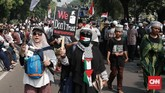 Massa aksi menunjukan poster dan alat peraga yang dibawa dalam kegiatan mengawal sidang putusan sengketa Pilpres 2019 di Mahkamah Konstitusi (MK) di kawasan Jalan Medan Merdeka Barat, Jakarta, 27 Juni 2019. (CNN Indonesia/Andry Novelino)