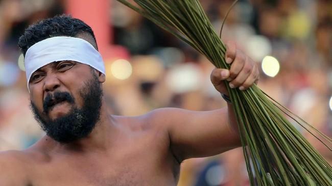 Ukuwala Mahiate diikuti 20 peserta dari kedua desa yang saling berhadapan dengan memegang sapu lidi di kedua tangan. Kedua kelompok mulai saling mengayunkan lidi saat suling mulai ditiup. (ANTARA FOTO/Atika Fauziyyah)