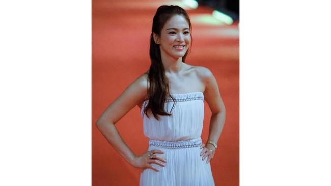 Ketika menghadiri berbagai undangan karpet merah, Song Hye Kyo terlihat lebih suka gaya aman yaitu gaya feminin dengan gaun cantik. (Photo by STR / AFP)