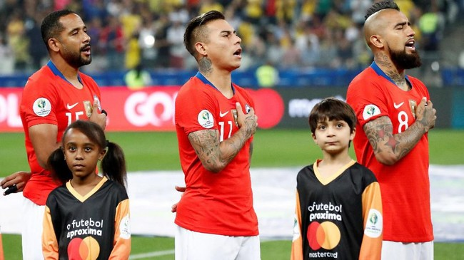 Jean Beausejour, Eduardo Vargas, dan Arturo Vidal menyanyikan lagu kebangsaan pada perempat final Copa America 2019 diStadion Arena Corinthians, Sao Paulo, Jumat (28/6) waktu setempat. (REUTERS/Henry Romero)