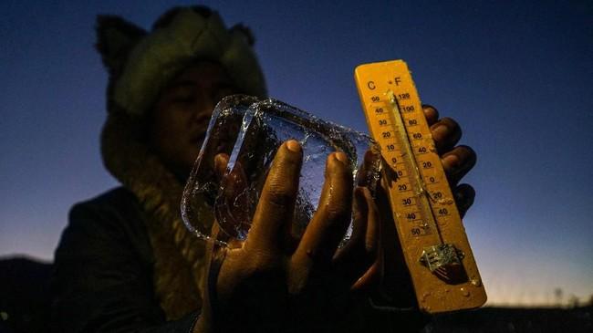 Petugas mengukur suhu udara di Dieng yang mencapai minus tujuh derajat Celcius, dan menyebabkan embun beku menyelimuti kompleks Candi Arjuna, di dataran tinggi Dieng, Banjarnegara, Jawa Tengah. (ANTARA FOTO/Idhad Zakaria/foc).