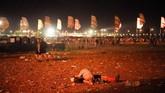 Sepasang penonton tak sungkan tidur di tengah lapangan usai menyaksikan konser di Glastonbury Festival 2019. (REUTERS/Henry Nicholls)