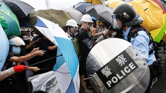 Sekitar 100 personel polisi anti-huru hara bersenjata pemukul karet bersiaga di belakang pecahan kaca ketika para demonstran masuk melalui jendela. (Reuters/Thomas Peter)
