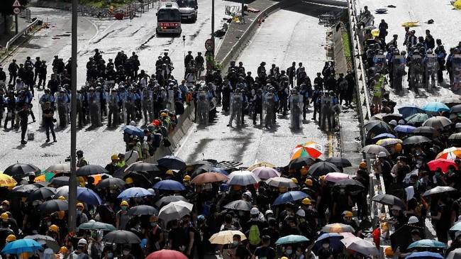 Aksi protes menolak RUU ekstradisi di Hong Kong pada Senin (1/7) kembali berakhir ricuh setelah sejumlah demonstran berupaya masuk ke dalam gedung parlemen dengan menabrakkan troli ke jendela. (Reuters/Thomas Peter)