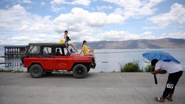 Pengunjung di Danau Erhai mengatakan kalau segala unsur alam di sekitar danau, mulai dari hewan liar sampai bunga berwarna-warni, menjadi faktor penting dalam perwujudkan fotonya. (REUTERS/Tingshu Wang)