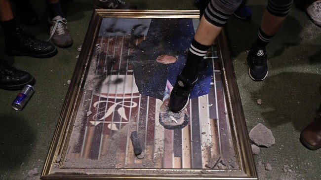 Para demonstran juga menginjak-injak dan merusak foto para pejabat pemerintahan di Hong Kong. (AP Photo/Vincent Yu)