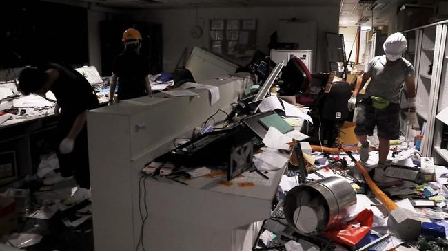 Massa demonstran merusak kaca lantas mencorat-coret bagian dalam gedung. Mereka juga menghancurkan sejumlah perlengkapan yang ada di dalamnya. (REUTERS/Tyrone Siu)