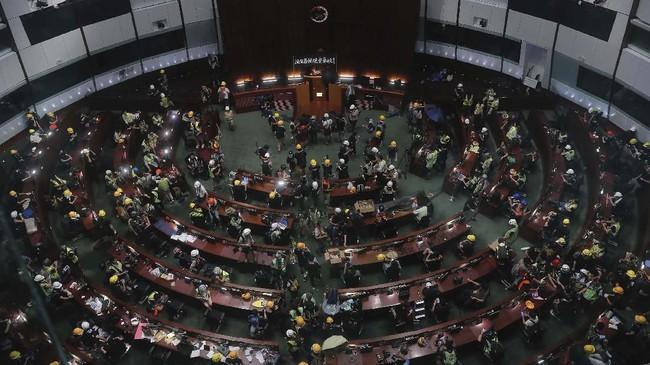 Ruang sidang di gedung parlemen Hong Kong juga tidak luput dari serbuan para demonstran. Mereka berdiri di atas meja sambil meneriakkan slogan anti pemerintah. (AP Photo/Kin Cheung)