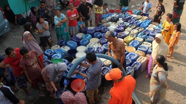 Petugas BPBD memberikan bantuan air bersih kepada warga yang dilanda kekeringan di kawasan Cibarusah, Kabupaten Bekasi, 1 Juli 2019. BPBD Kabupaten Bekasi mengedrop sebanyak 5000 liter air bersih per hari ke sejumlah wilayah kecamatan yang dilanda kekeringan. (ANTARA FOTO/Risky Andrianto)