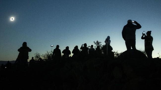 Sementara itu di Argentina warga berbondong-bondong menyaksikan gerhana di perbatasan di kota Cuyo. (AP Photo/Esteban Felix)