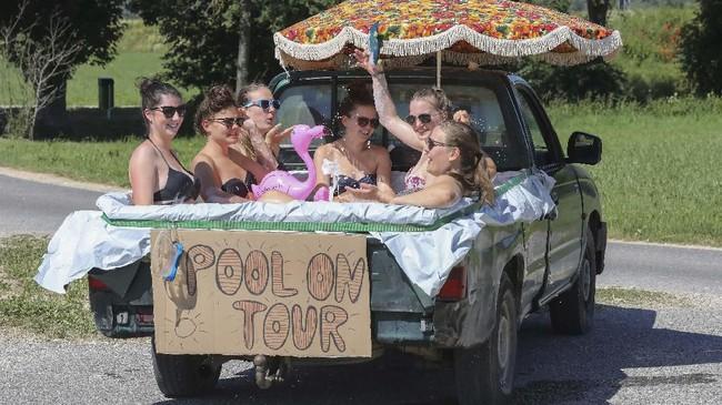 Di Unlingen, Jerman bagian selatan, enam perempuan mendinginkan badan di air di suatu bak mobil pick-up yang dilapisi plastik. Jerman adalah satu dari beberapa tempat yang diterpa gelombang panas pada pekan ini. (Thomas Warnack/dpa via AP)