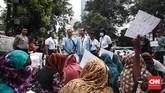 Pihak UNHCR memberikan penjelasan kepada pencari suaka yang berasal dari Afghanistan dan Somalia yang bertahan tinggal di depan Menara Rafindo, Jakarta, Jumat, 5 Juli 2019. (CNNIndonesia/Safir Makki)