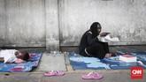 Pencari suaka asal Somalia menikmati nasi kotak di trotoar di kawasan Kebon Sirih, Jakarta, Jumat, 5 Juli 2019. (CNNIndonesia/Safir Makki)