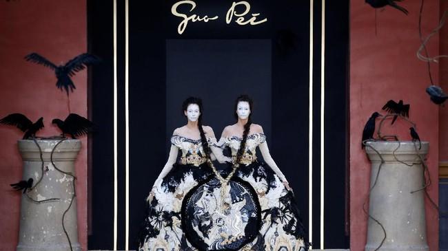 Bak kembar siam, tubuh dua model dibiarkannya melenggok dalam satu balutan gaun. Tampilan ini menantang standar pakaian sebagai produk yang bersifat singular dan personal. (REUTERS/Regis Duvignau)