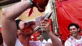 Rakyat tumpah ruah untuk menonton festival. Seorang peserta terlihat meminum anggur merah dari sepatu sebelum festival dimulai. (REUTERS/Susana Vera)
