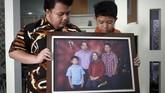 Muhammad Ivanka Rizaldi Nugroho (kiri) dan Muhammad Aufa Wikantyasa Nugroho (kanan). Dua putra mendiang Kepala Pusat Data Informasi dan Humas BNPB Sutopo Purwo Nugroho menunjukkan foto keluarga di rumah duka Raffles Hils, Cimanggis, Depok, Jawa Barat, Minggu (7/7). (ANTARA FOTO/Yulius Satria Wijaya)