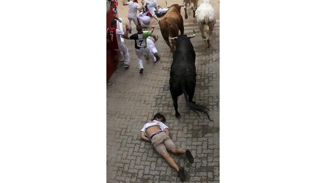Seseorang terbaring di tanah dan tak bisa bangun setelah jatuh di pantu masuk arena adu banteng. (REUTERS/Jon Nazca)