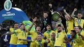 Kapten timnas Brasil Dani Alves yang dinobatkan sebagai pemain terbaik turnamen mengangkat trofi Copa America 2019 yang disambut gembira oleh rekan-rekan setimnya usai mengalahkan timnas Peru 3-1. (REUTERS/Ueslei Marcelino)