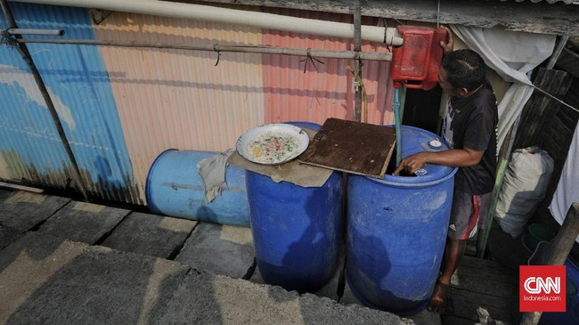 Warga memperbaiki instalasi penampungan air hujan miliknya di Kampung Nelayan Kamal Muara, Jakarta Utara, 9 Juli 2019. (CNN Indonesia/Adhi Wicaksono)