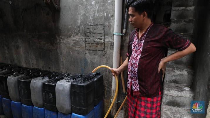 Warga mencuci pakaian di depan rumahnya di Kawasan Muara Baru,   Jakarta Utara. Warga mengaku, kebutuhan air mereka tidak pernah terpenuhi sepanjang tahun.  Air PAM tidak mengalir di daerahnya, untuk memenuhi kebutuhan air sehari-hari, warga harus membeli ke pedagang air bersih yang ada di depan gang. Minimal, dalam sehari mereka mengeluarkan uang Rp. 15.000 untuk membeli enam derigen air bersih. Biasanya air yang digunakanuntuk mencuci pakaian dan memasak. (CNBC Indonesia/Muhammad Sabki)