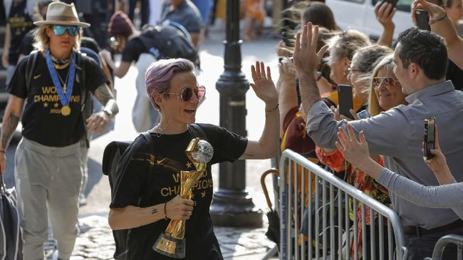 Bintang timnas Amerika Serikat, Megan Rapinoe memberi salam kepada para penggemar yang sudah menunggu kedatangan tim. (REUTERS/Andrew Kelly)