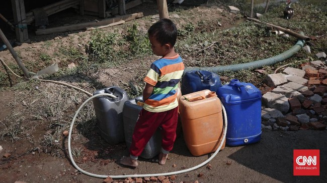 Seorang anak mengisi air ke dalam jeriken di Desa Ridomanah, Cibarusah, Jawa Barat, Rabu (10/7). (CNNIndonesia/Safir Makki)