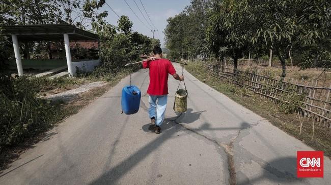 Bermodalkan dua jeriken, warga Desa Ridogalih berjalan menuju rumah usai mengambil air bersih gratis. (CNNIndonesia/Safir Makki)