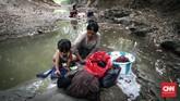 Warga Desa Ridogalih mencuci pakaian dan mandi di Kali Cihoe Desa Ridogalih, Cibarusa, Kabupaten Bekasi. Kemarau membuat sumur di rumah kering. (CNNIndonesia/Safir Makki)