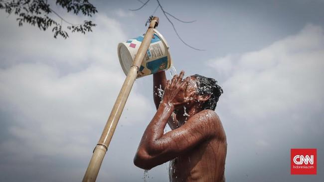 Warga membasuh muka dari air penampungan di Desa Sirna Jati, Cibarusah. Air ini hanya mereka gunakan untuk mencuci dan mandi. (CNNIndonesia/Safir Makki)