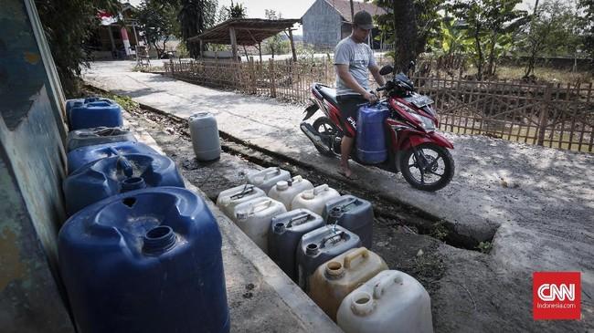 Anwar menggunakan motor untuk mengangkut jeriken air yang diambil dari MCK umum di Desa Ridogalih, Cibarusah, Kabupaten Bekasi, Rabu (10/7). (CNNIndonesia/Safir Makki)