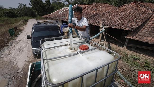 Warga menggunakan mobil mengisi air ke dalam tengki besar. Pompa dan selang besar diarahkan ke aliran sungai Cihoe, Desa Ridomanah. (CNNIndonesia/Safir Makki)