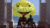Orang-orang duduk di bangku di Promenade des Anglais di hadapan desain 'wajah bahagia' parascending selama musim panas yang cerah di Nice, Prancis. (10 Juli 2019. REUTERS / Eric Gaillard)