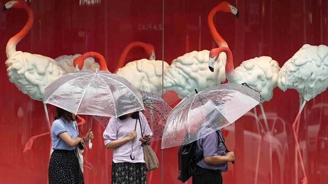 Orang-orang berjalan di bawah hujan dekat tempat perbelanjaan di Tokyo.(AP/Eugene Hoshiko)