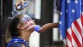 Salah satu fan timnas AS menghiasi wajah bermotif bendera Amerika Serikat dengan menggunakan cat semprot. (Mandatory Credit: Brad Penner-USA TODAY Sports)