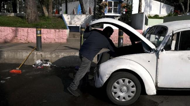 Seorang mekanik tengah melihat kap mobil VW Beetle. Bagian depan untuk meletakan barang bawaan, sementara mesin tersimpan di balik kap belakang. (AP Photo/Cristina Baussan)