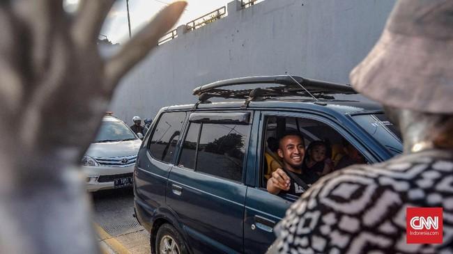 Merasa terhibur dengan aksi para manusia perak, seorang pengemudi tersenyumdan memberikan tanda apresiasi dalam bentuk uang. (CNN Indonesia/Daniela)