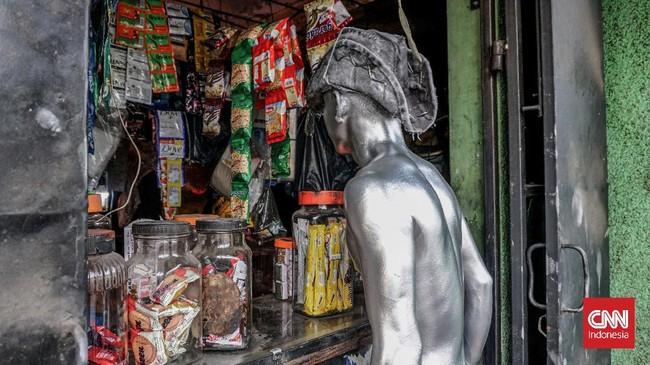 Di waktu istirahat, mereka juga menyempatkan diri untuk membeli minuman di warung setempat dengan sekujur cat di tubuh. (CNN Indonesia/Daniela)