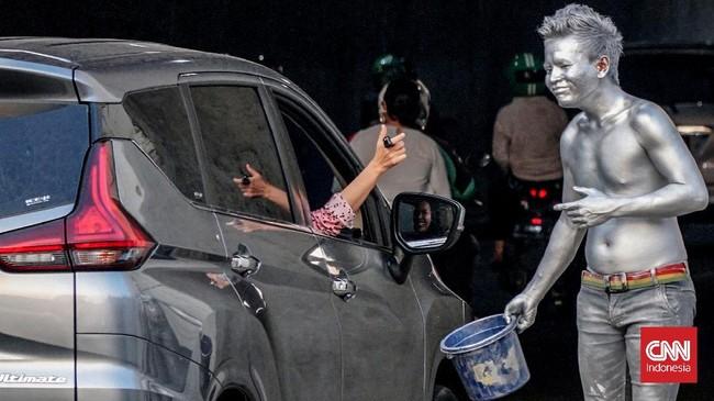 Seorang pengemudi terlihat memberikan tanda apresiasi dalam bentuk uang. (CNN Indonesia/Daniela)