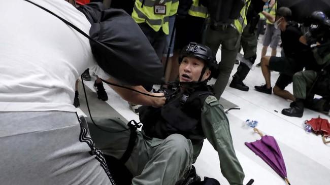 Para demonstran juga membalas sikap represif polisi dengan melemparkan payung yang mereka bawa. (REUTERS/Tyrone Siu)