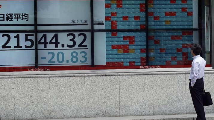 People walk past an electronic stock board showing Japan's Nikkei 225 index at a securities firm in Tokyo Wednesday, July 10, 2019. Asian shares were mostly higher Wednesday in cautious trading ahead of closely watched congressional testimony by the U.S. Federal Reserve chairman. (AP Photo/Eugene Hoshiko)