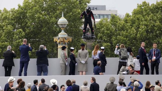 Ketika melihat papan terbang itu, para pengunjung bersorak dan berkeliling di atas Champs-Elysees ketika parade militer dilakukan (REUTERS/Pascal Rossignol)