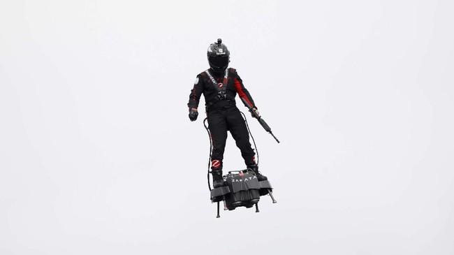 Seorang pengusaha dan inovator Perancis, Franky Zapata, terbang menggunakan papan terbang (hover board) di langit Paris, Kamis (14/7). (REUTERS/Charles Platiau)