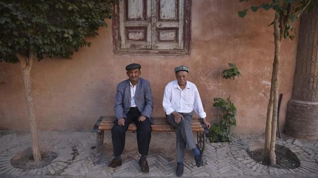 Pria-pria Uighur di Kashgar. Sementara turis diperlihatkan sisi Xinjiang yang adat, seni budaya, dan tradisinya telah dikurasi, sekitar 1 juta warga Uighur dan minoritas Muslim menghuni kamp yang dikontrol ketat pemerintah China. (GREG BAKER/AFP)