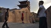 Turis berfoto di Kashgar, Xinjiang, China.Dari bukit pasir yang luas di Gurun Taklamakan sampai ke puncak-puncak yang tertutup salju di Tianshan, pemerintah China menjual kawasan Xinjiang yang sedang bermasalah sebagai destinasi wisata. (GREG BAKER/AFP)