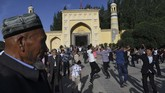 Pria-pria Uighurmenari setelah salat Idulfiridi Masjid Id Kah, Kashgar.Pada tahun 2020, Xinjiang memiliki target 300 juta kunjungan wisatawan dan memperoleh pendapatan US$ 87 miliar.(GREG BAKER/AFP)