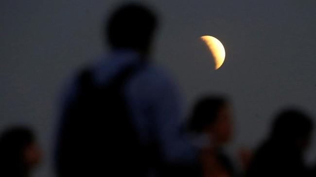 Gerhana bulan sebagian terjadi ketika bulan melewati bayangan sebagian Bumi (penumbra) sehingga membuat sebagian sisi yang dilewati bayangan nampak lebih gelap (umbra). (REUTERS/Adriano Machado)