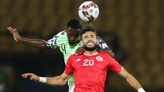 Gelandang Tunisia Ghailene Chaalali susah-payah duel udara dengan gelandang Nigeria Wilfred Ndidi. Ndidi masih tercatat sebagai pemain Leicster City. (REUTERS/Sumaya Hisham)